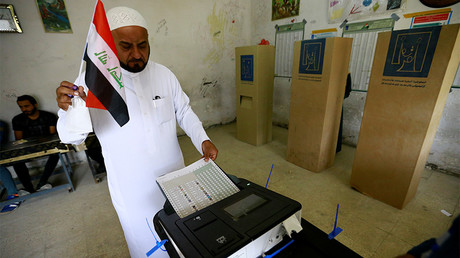 An Iraqi man casts his vote at a polling station during the parliamentary election in Baghdad © Thaier Al-Sudani