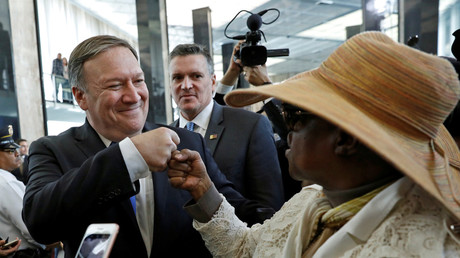 New United States Secretary of State Mike Pompeo fist bumps with a woman upon his arrival during his first day at the State Department in Washington, U.S., May 1, 2018. © Kevin Lamarque