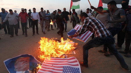 Palestinian demonstrators burn representations of US flags and a poster of Donald Trump in the southern Gaza Strip May 15, 2018. © Ibraheem Abu Mustafa