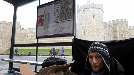 Stuart, a homeless man, sits under a bus shelter where he sleeps opposite Windsor Castle in January. © Toby Melville