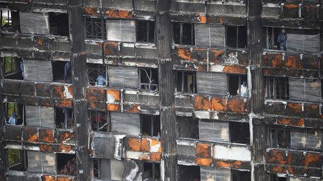 Workers stand inside the burnt out remains of the Grenfell tower in October, 2017.  © Hannah Mckay