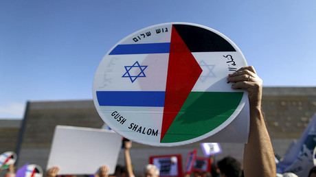 A demonstrator holds a sign with a Palestinian and Israeli flag during a demonstration by Palestinian and Israeli activists calling for a better future for both people, in the West Bank city of Bethlehem. © Ammar Awad