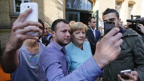 Migrants from Syria and Iraq take selfies with German Chancellor Angela Merkel on September 10, 2015. © Fabrizio Bensch / Reuters