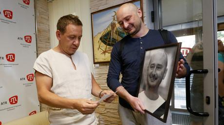 Russian dissident journalist Arkady Babchenko (R) holds his own memorial portrait in Kiev, Ukraine on May 31, 2018. © Valentyn Ogirenko