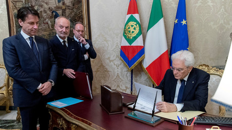 Italy's PM-designate Giuseppe Conte looks on as President Sergio Mattarella signs documents © Presidential Press Office