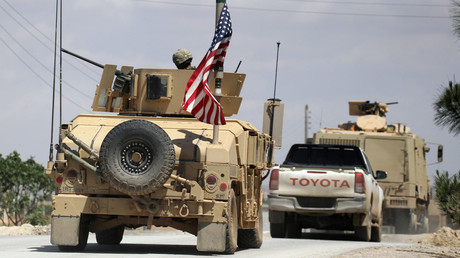 FILE PHOTO: The US flag flutters on a military vehicle in Manbij countryside, Syria, on May 12, 2018. © Aboud Hamam