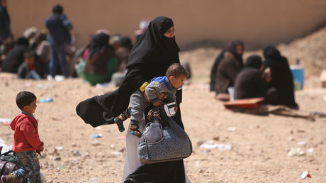 A woman carries her child as they flee from Raqqa city. © Rodi Said