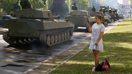 A woman takes pictures during a rehearsal for the Victory Day parade in Donetsk,  May 3, 2018. © Alexander Ermochenko
