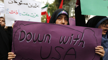 Iranian women carry anti-US signs during a demonstration outside the former US embassy in Tehran © ATTA KENARE