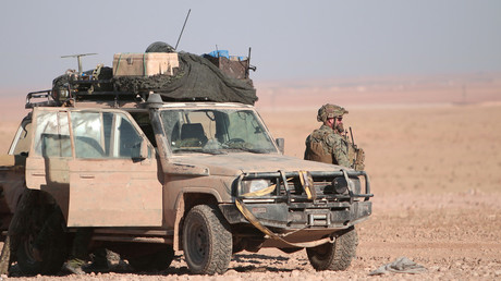 FILE PHOTO: A US fighter stands near a military vehicle, north of Raqqa city © Rodi Said