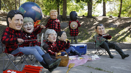 Oxfam activists wearing giant papier mache heads depicting G7 leaders pose during a demonstration in Canada © Chris Wattie