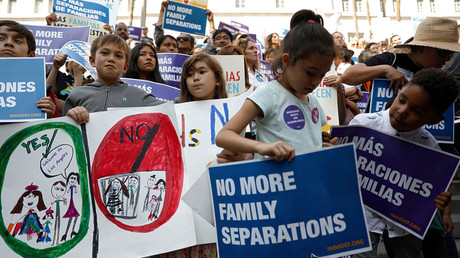 People hold signs to protest against the separation of families at the US-Mexico border. © Patrick Fallon / Reuters