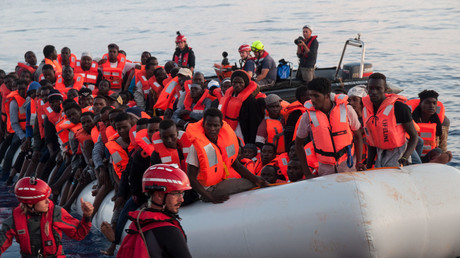 Migrants on an inflatable boat rescued boarding the 'Lifeline' sea rescue boat at sea on June 21, 2018. © Mission Lifeline