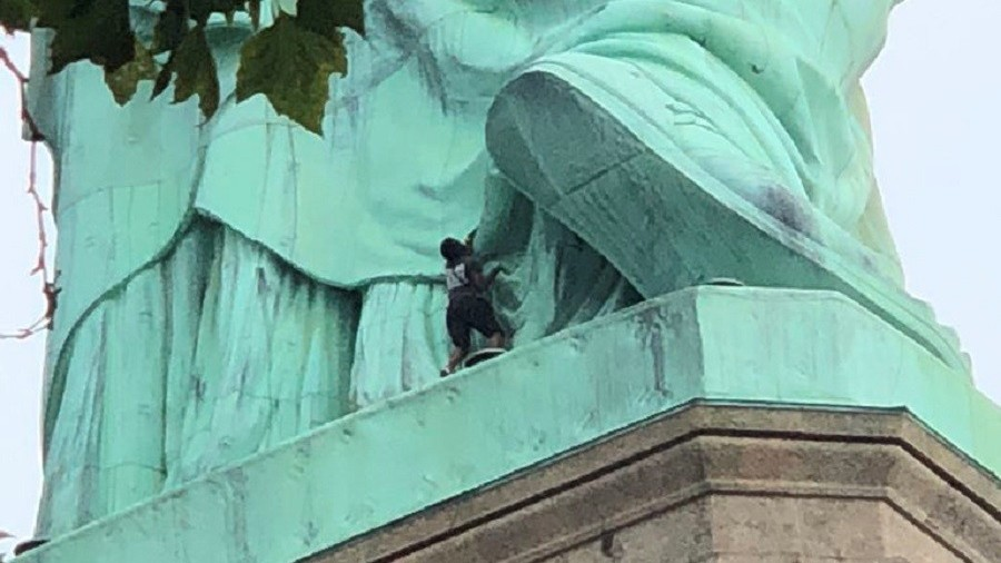 Anti-ICE protester scales Statue of Liberty, prompting island evacuation & rescue (VIDEO)