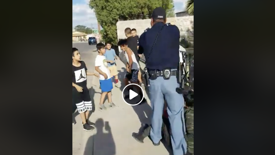 'Why is he picking on little kids?' Footage shows cop pointing gun at children