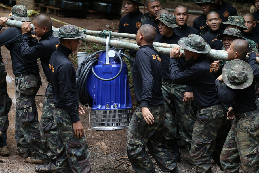 Military personnel carry a water pump machine as they enter the Tham Luang cave complex