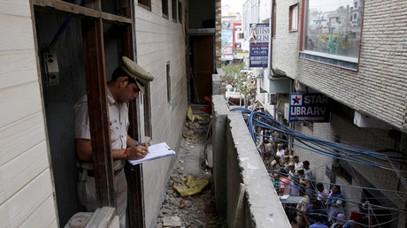 A policeman writes notes in the house where the bodies of eleven members of a family were found dead © Stringer