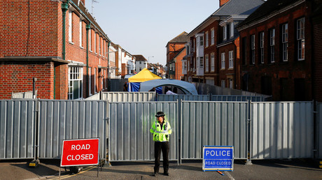 A police officer stands in front of screening erected behind John Baker House after two people had been poisoned with nerve agent. © Henry Nicholls