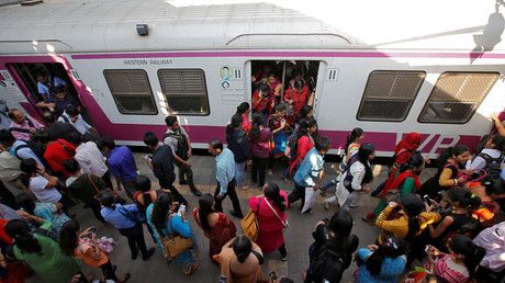 Commuters disembark from a suburban train at a railway station in Mumbai. © Shailesh Andrade