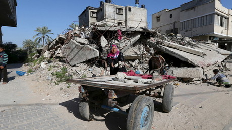 Palestinian woman collects bricks for sale from the site of a destroyed house in the Gaza Strip © Khan Younis