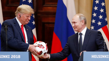 Donald Trump receives a football from Russian President Vladimir Putin in Helsinki, Finland July 16, 2018