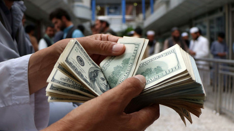 FILE PHOTO: A money changer counts US dollar banknotes at a market in Herat province, Afghanistan, on June 3, 2018. © Jalil Ahmad