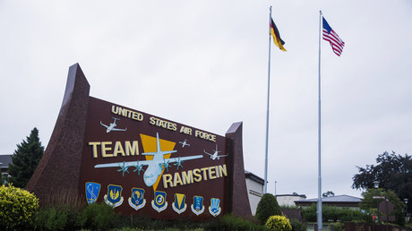 The flags of the United States and Germany fly behind a sign at Ramstein Air Base © Lucas Jackson