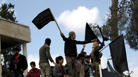 Protesters carry Nusra Front flags during an anti-government protest in the town of Marat Numan in Idlib province, Syria, March 11, 2016. © Khalil Ashawi