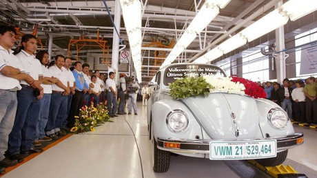 VW workers watch the very last VW Beetle as it rolls off the production line at VW's Puebla plant 30 July, 2003, Mexico © Andrew Winning