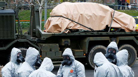Soldiers wearing protective clothing gather after removing vehicles from a car park in Salisbury, Britain, March 11, 2018. © Henry Nicholls