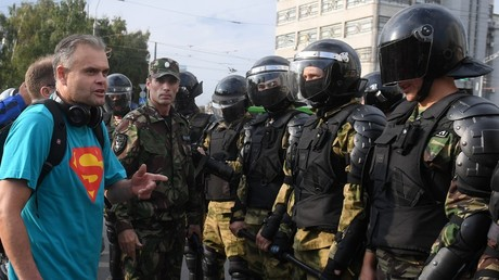 A protester confronts a riot police cordon in Moscow