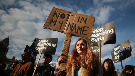 Protesters hold placards during a demo against bombing Syria outside parliament, London, April 16, 2018.  © Hannah Mckay