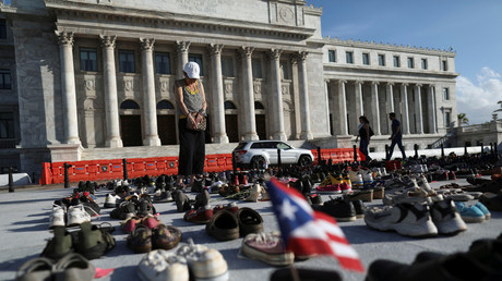 A woman pays respects at a collection of shoes left outside Puerto Rico's capitol to honor the victims of Hurricane Maria © Alvin Baez