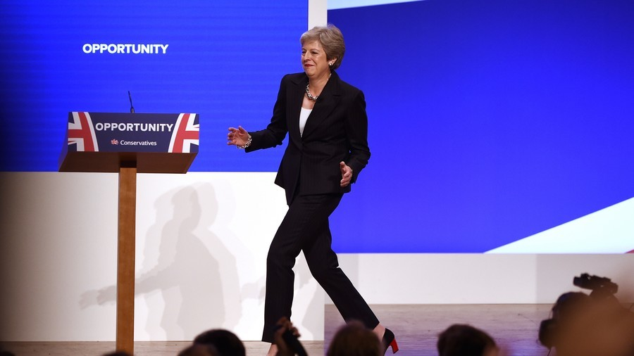 British PM May defends Brexit plan after dancing onto stage