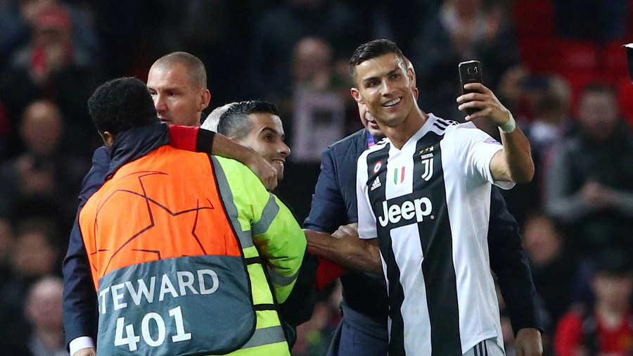 Football selfie of the year? Security-restrained pitch invader snags snap with Ronaldo! (PHOTOS)