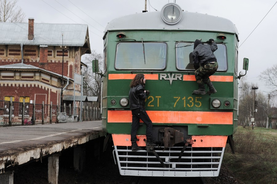 Two young men cling to a commuter train in Russia's Leningrad Region