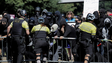 Police officers hold back Antifa protesters at a rally in Portland © Reuters / Elijah Nouvelage