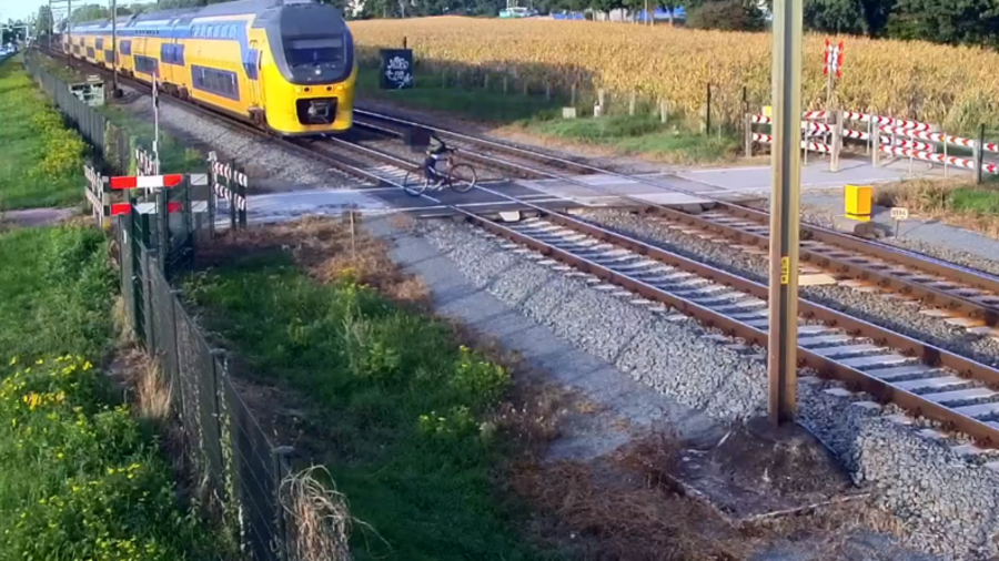 Split-second from disaster: Cyclist cheats death after failing to spot oncoming train (VIDEO)
