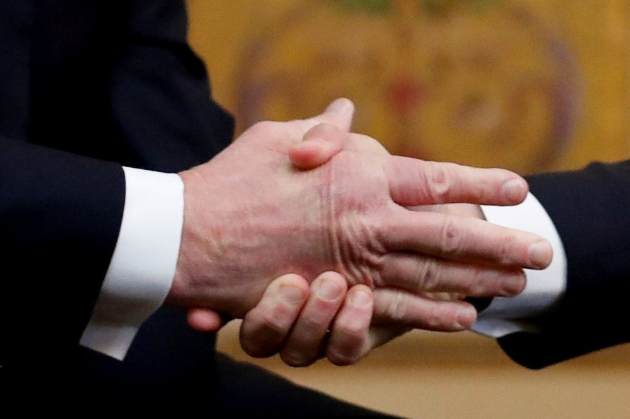 Emmanuel Macron shakes Donald Trump's hand as they meet on Staurday
