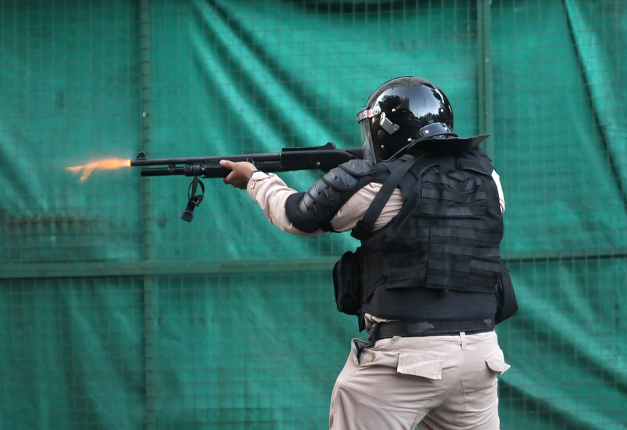 A riot policeman fires his gun after the match was postponed