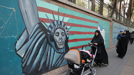 Iranian women walk past an anti-US mural in Tehran © AFP / Atta Kenare