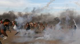 Palestinian protesters in Gaza Strip flee tear gas fired by Israeli troops, October 5, 2018