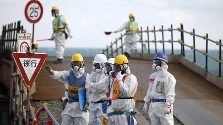 Workers, wearing protective suits and masks, are seen near the No. 3 and No.4 reactor buildings at Fukushima Daiichi nuclear power plant © Reuters / Toru Hanai