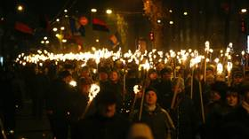 Activists of Ukrainian nationalist parties hold torches as they take part in a rally to mark the anniversary of the birth of Bandera in Kiev