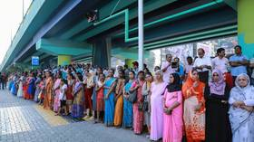 Indian women stand in a line to take part in a