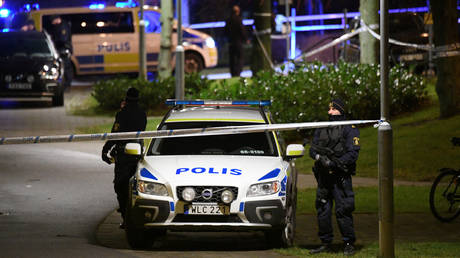Officers standing next to police vehicles in Rosengard, Malmo © TT News Agency via REUTERS/Johan Nilsson