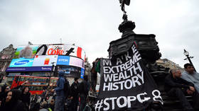 Anti-capitalist protesters hang a banner underneath the statue of Eros in Piccadilly Circus, London © AFP / Leon Neal