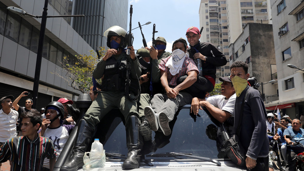 Caracas warns they'd use weapons if needed as crowds of coup supporters flock to presidential palace