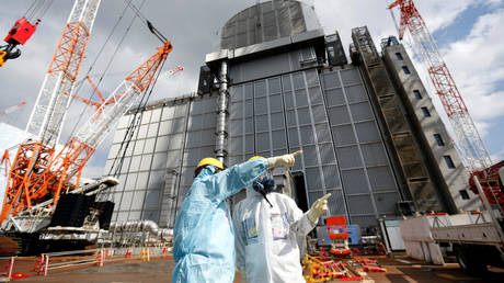 TEPCO employees in front of the No. 3 reactor building where the removal of atomic fuel began on Monday in Fukushima. © Reuters / Issei Kato