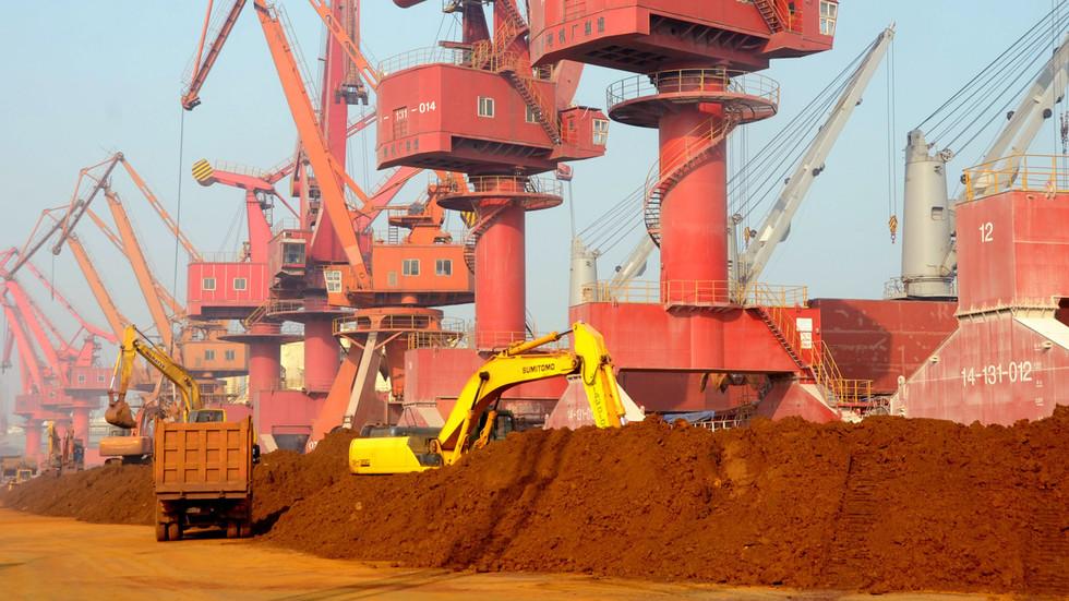 Escavadeira carrega mineral raro no porto de Lianyungang, China